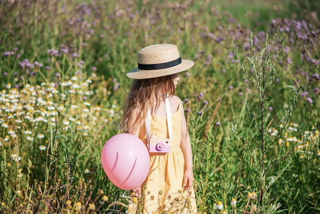 Cute little girl walking in the flowers field in yellow dress and hat, summer time