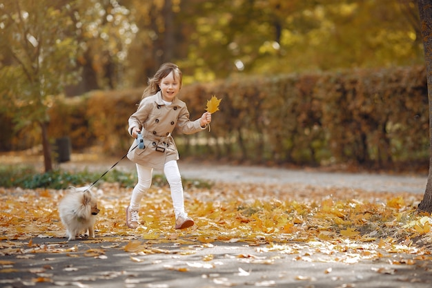 Cute little girl walks in a autumn park with a dog