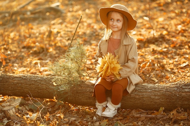 かわいい女の子が秋の公園で散歩します。