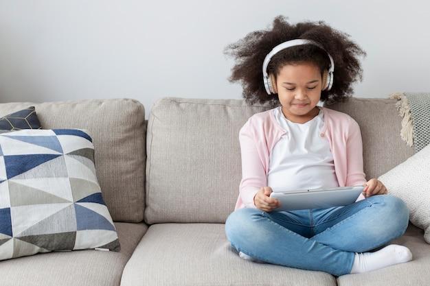 Cute little girl watching cartoons at home