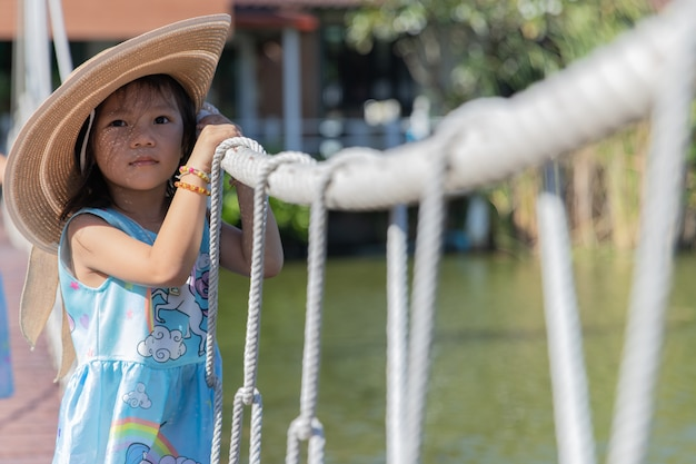 Cute little girl wear a big hat and holding rope bridge
