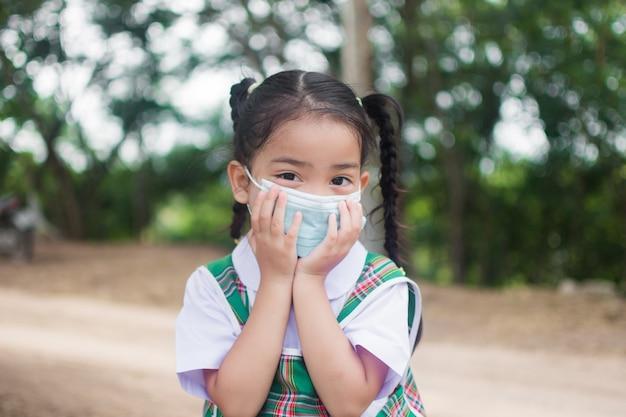 귀여운 소녀는 코로나 바이러스 또는 코로나 바이러스 19 보호를 위해 마스크를 착용합니다.