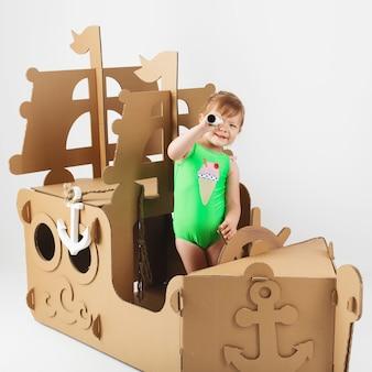 Милая маленькая девочка в ярком купальнике играет с картонным кораблем на белом