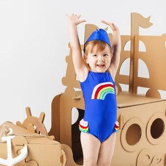 Милая маленькая девочка в ярком купальнике играет с картонным кораблем