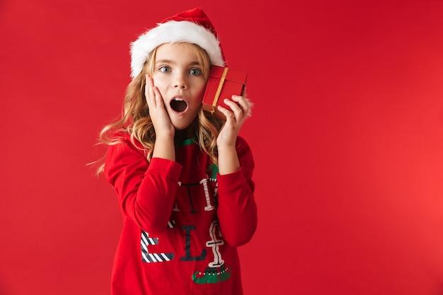 크리스마스 모자 서 절연, 선물 상자를 들고 입고 귀여운 소녀