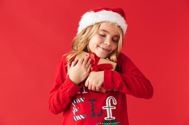 孤立して立って、プレゼントボックスを持ってクリスマス帽子をかぶってかわいい女の子