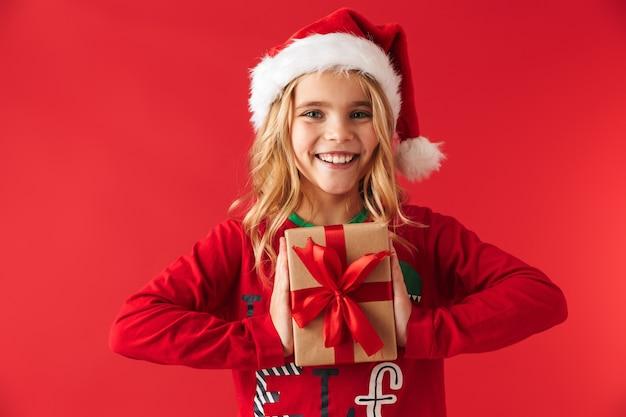 Милая маленькая девочка в рождественской шляпе стоя изолированно, держа настоящую коробку