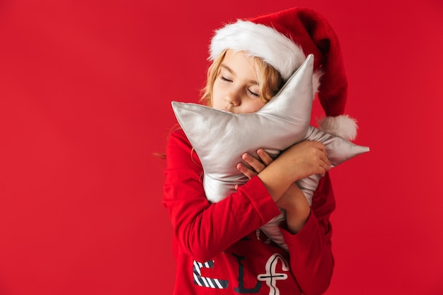 Милая маленькая девочка в рождественской шапке стоит изолированно, держа подушку в форме звезды