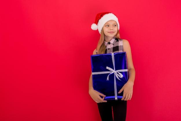 파란색 선물 상자를 들고 빨간색 배경 위에 절연 크리스마스 모자 서 입고 귀여운 소녀