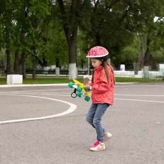 Милая маленькая девочка в шлеме катается на скейтборде в красивом летнем парке