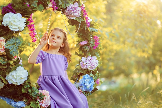 Cute little girl wearing lilac dress posing while sitting in ring decorated with flowers at the park summertime