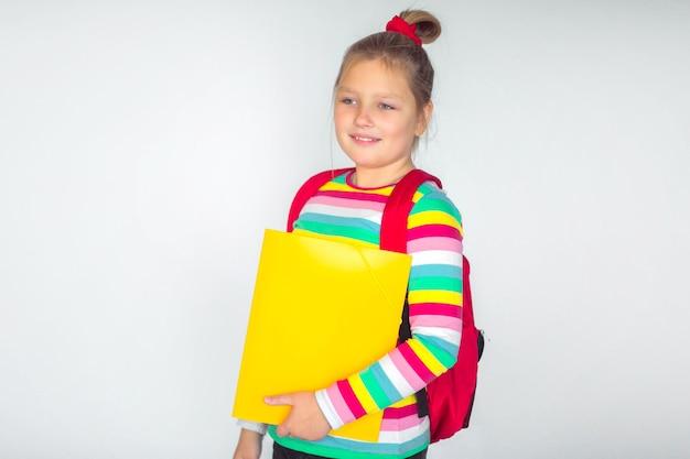 白い背景の上に立っている赤いバックパックを身に着けているかわいい女の子、テキストの場所、学校のコンセプトに戻る