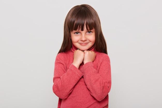 Милая маленькая девочка в красном свитере повседневного стиля со счастливой застенчивой улыбкой, держа кулаки под подбородком, позирует изолированной над белой стеной.