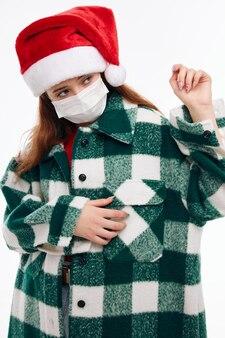 Милая маленькая девочка в шляпе санта медицинская маска в клетку крупным планом. фото высокого качества