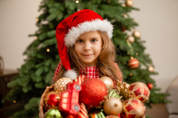 Cute little girl wearing santa hat while holding basket with christmas decorations