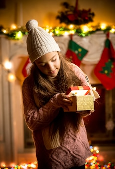 Cute little girl wearing sweater looking in gift box at christmas eve