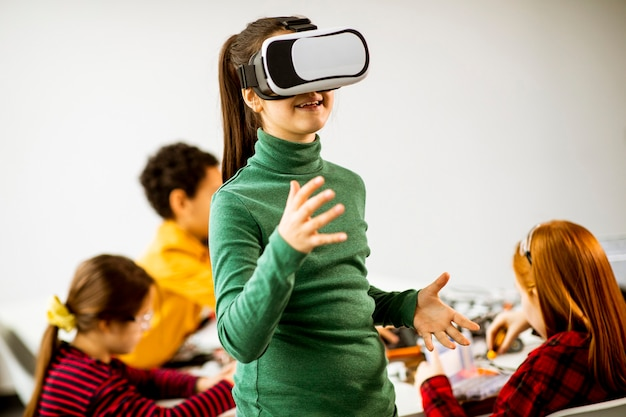 Cute little girl wearing vr virtual reality glasses in a robotics classroom