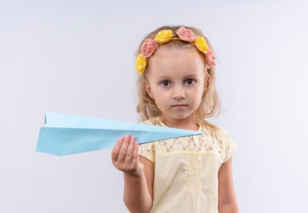 Una bambina sveglia che indossa la camicia gialla in aeroplano di carta di volo della fascia floreale mentre osservava su una parete bianca