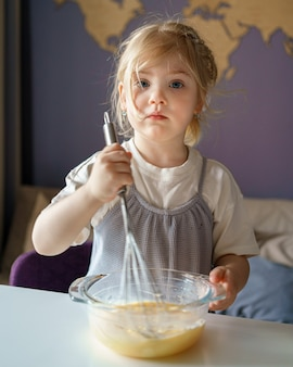 Милая маленькая девочка взбивает яйца в миске