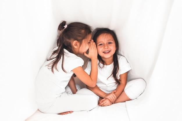 カバーの下で彼女の妹に何かをささやくかわいい女の子