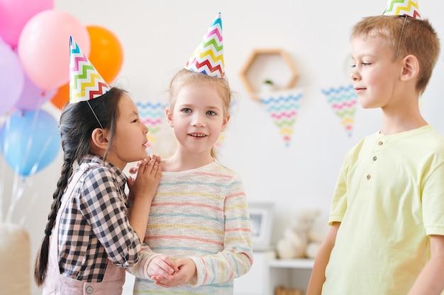 Милая маленькая девочка шепчет что-то одному из своих друзей на домашнем дне рождения во время игры после праздничного ужина