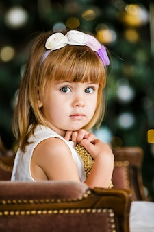 Cute little girl in the white dress with nice wreath near the christmas tree