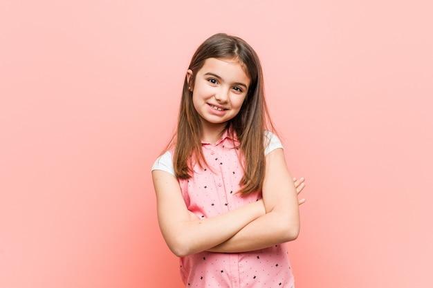Милая маленькая девочка, которая чувствует себя уверенно, скрещивая руки с решимостью.