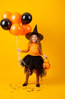Cute little girl in a witch costume for halloween