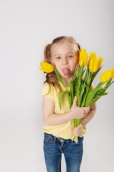 黄色のtシャツとブルージーンズの黄色いチューリップの花束を持つかわいい女の子