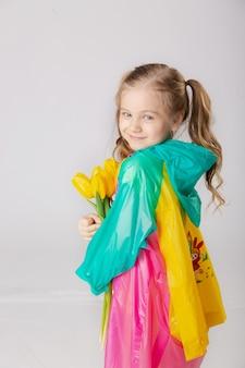 明るいレインコートと花の傘を持つかわいい女の子