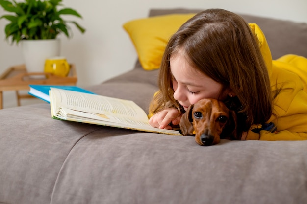 Милая маленькая девочка с таксой лежит на кровати и читает книгу открытая книга лежит на кровати