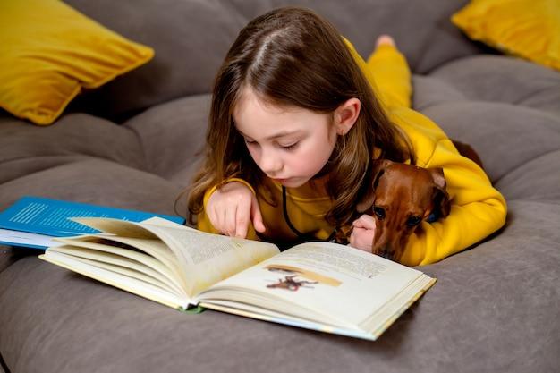 Милая маленькая девочка с собакой лежат на кровати и читают книгу, открытая книга лежит на кровати