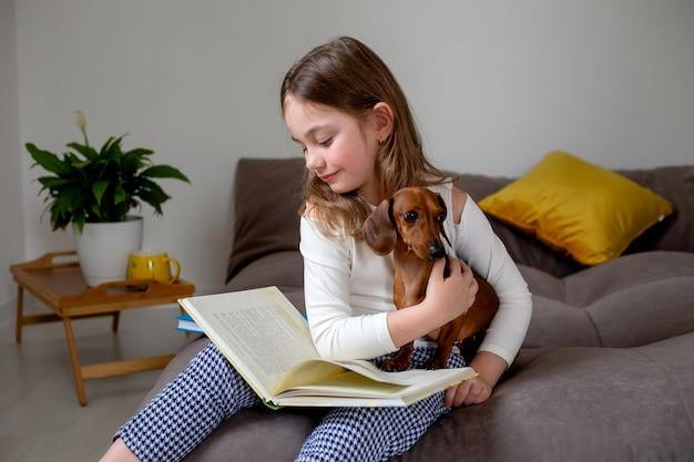 Милая маленькая девочка с карликовой таксой сидит на кровати и читает