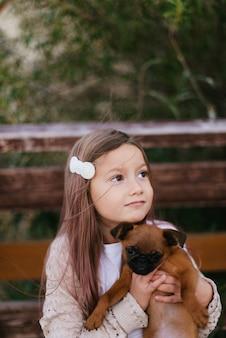 개를 들고 그녀의 머리에 머리핀을 가진 귀여운 소녀