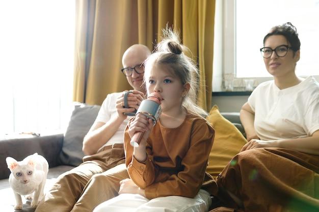 집에서 그녀의 부모를 위해 노래방 마이크 노래와 함께 귀여운 소녀