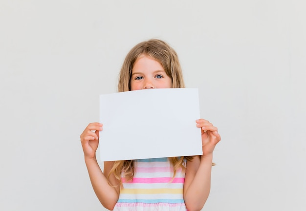 흰색 빈 종이와 함께 귀여운 소녀. 흰색 배경에 고립.