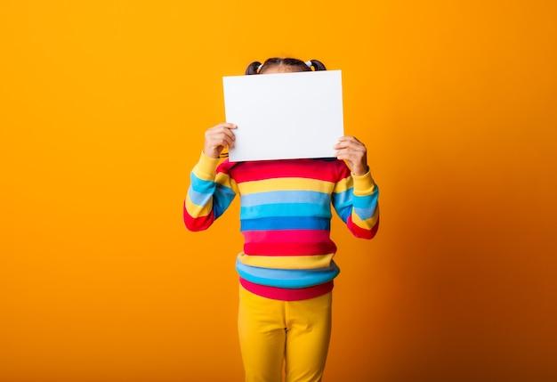 흰 종이를 들고 있는 귀여운 소녀. 노란색 배경 빈 종이를 들고 어린 소녀