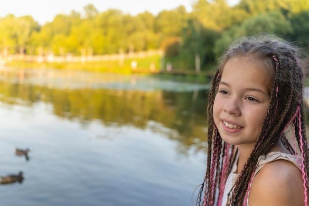 Милая маленькая девочка с африканскими косичками на фоне озера и пляжа крупным планом