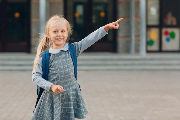 Милая маленькая девочка с рюкзаком, возвращаясь в школу и указывая путь ее пальцем.