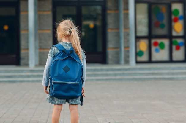 Милая маленькая девочка с рюкзаком возвращается в школу