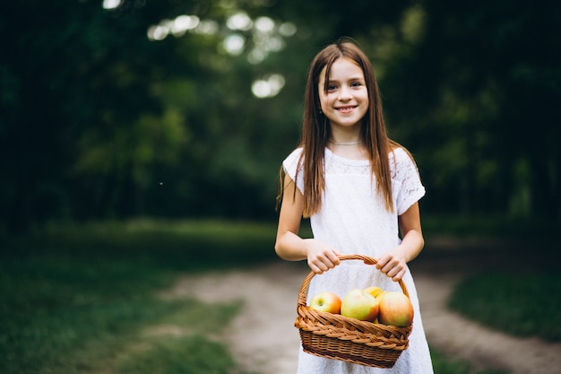 Cute little girl with basket of fruit