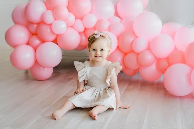 ピンクの風船で座っているベージュのドレスでブロンドの髪のかわいい女の子。幸せな瞬間、美しい誕生日の子。ベビーシッター。