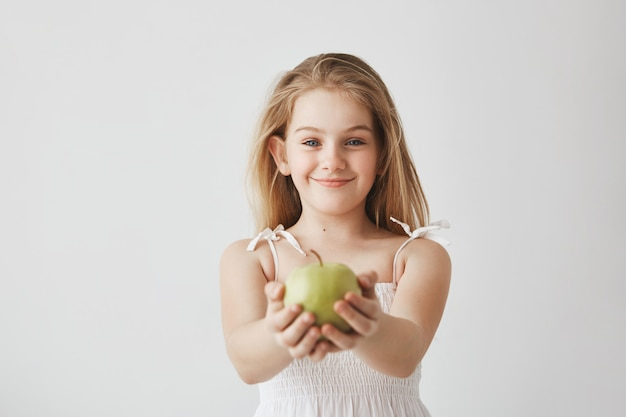 Cute little girl with blond long hair and blue eyes in white dress smiling, holding apple in hands and showing