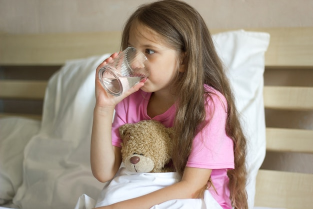 Cute little girl with blond sits on the bed holds glass of water drinks water and hugs teddy bear