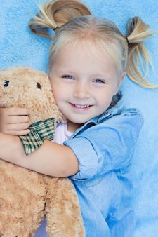 Cute little girl with blonde hair lying on the bed with stuffed teddy bear