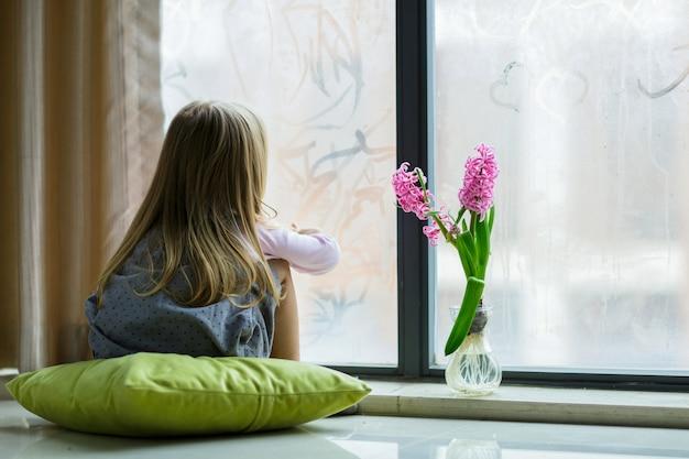 Милая маленькая девочка со светлыми волосами, роспись дома на окне