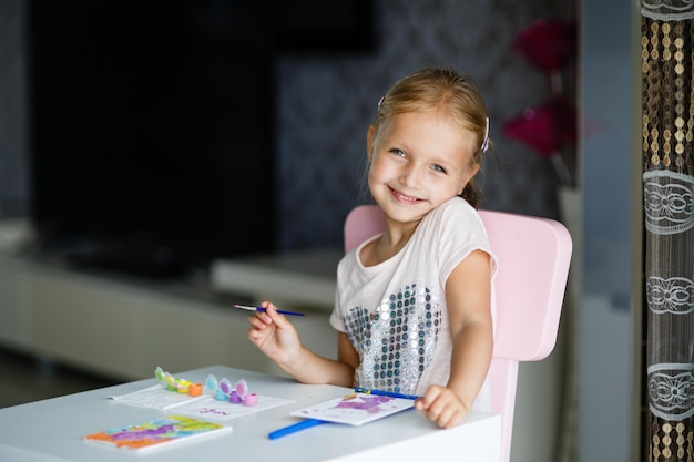 Cute little girl with blonde hair painting picture at home.