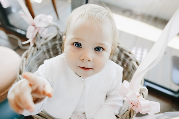 Cute little girl with blue eyes sits in a basket