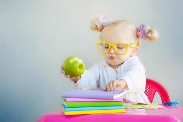 Cute little girl with books and green apple