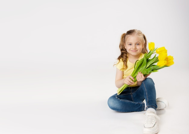 Cute little girl with a bouquet of yellow tulips in yellow t-shirt and blue jeans